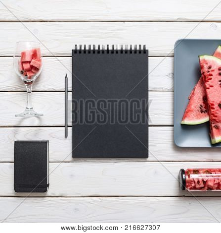 Black sketchbook on white kitchen table with sliced watermelon. Top view.