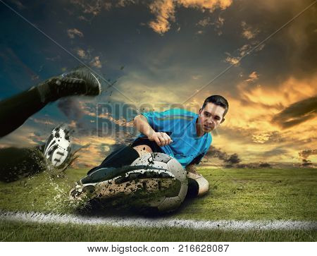 Soccer player in dynamic action on the green grass field under sunset sky with clouds