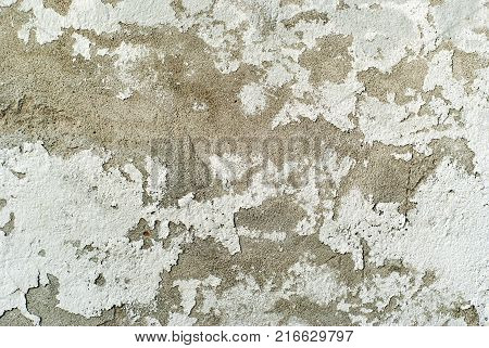 texture background: old concrete wall with peeling plaster and crumbling whitewash