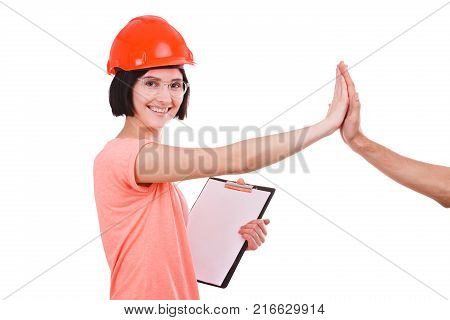 A beautiful girl with a smile in the helmet of a contractor gives five and looks to the side on a white isolated background