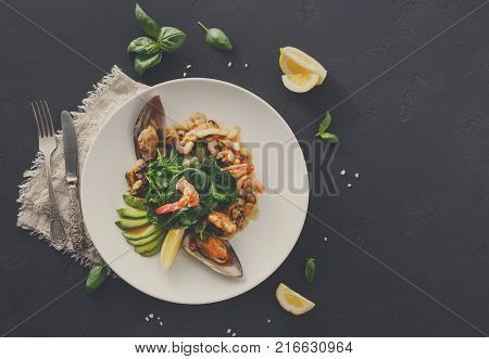 Warm salad with grilled seafood flat lay. Top view on plate with mix of roasted shrimps, mussels and squid, restaurant serving