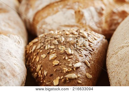Bread background. Bread assortment with white and rye buns, focus on whole grain triangle bun, closeup
