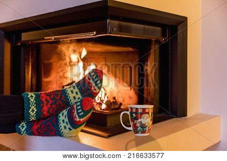 Feet in woollen socks by the Christmas fireplace. Legs in wool socks at a modern Christmas fireplace. Close up on feet. Winter and Christmas holidays concept.