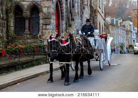 Jim Thorpe PA USA - December 3 2017: Horse wearing Santa hats and reindeer antlers pull a white carriage through the picturesque town.