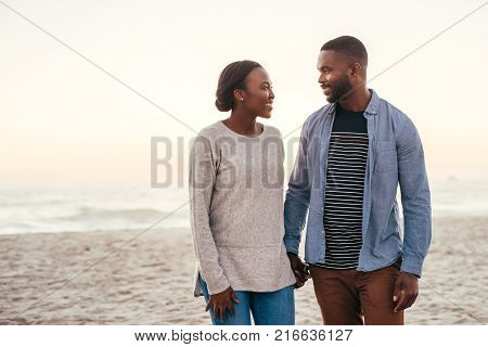 Smiling young African couple walking together down at sandy beach at sunset holding hands and talking