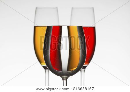 Three wineglasses different colour fluids that distort the refraction