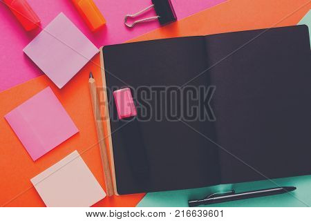 Stationery at modern creative work space. Stylish open notepad with black pages, paperclip, markers, pencil and memo notes on abstract multicolored background, top view, copy space