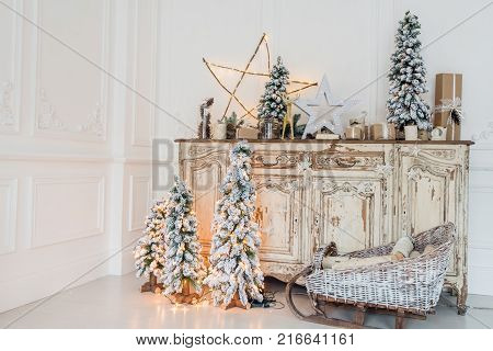 Christmas decoration on ancient vintage old commode chest of drawers. Hand made craft gifts, candels and a tree at background