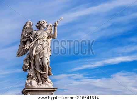 Angel holding the Holy Lance of Longinus with beautiful sky and copy space. A 17th century baroque masterpiece at the top of Sant'Angelo Bridge in the center of Rome