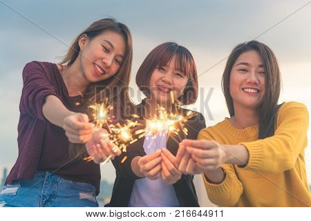 Outdoor shot of young people at rooftop party. Happy group of asia girl friends enjoy and play sparkler at roof top party at evening sunset. Holiday celebration festive party. Teenage lifestyle party. poster