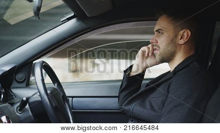 Stressed young businessman swearing and talking phone while sitting inside car outdoors
