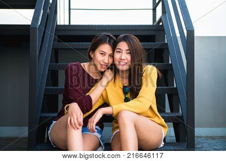 LGBT lesbian women couple moments happiness. Lesbian women couple together outdoors concept. Lesbian couple embraced together relation fall in love. Two asian women having fun together at rooftop. poster