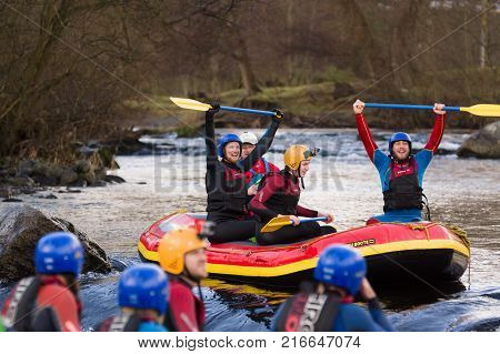 Llangollen Wales UK - January 28 2017: A happy team of white water rafters cheering having just made a descent of the rapids on the River Dee North Wales