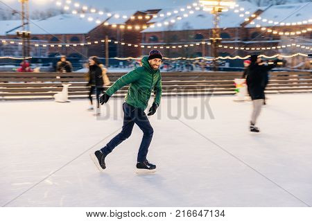 Outdoor Shot Of Unexperienced Male Skater Uses Skate Aid For Go Skating On Ice, Being In Good Mood,