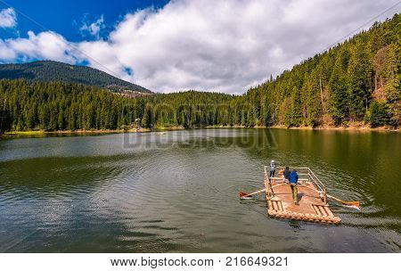 Synevyr Ukraine - May 09 2017: wooden raft with tourists on Synevyr lake. Beautiful springtime nature scenery in the most visited location of Carpathian mountains
