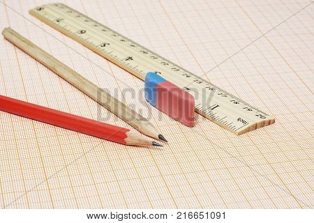 On the millimeter paper there are two simple pencils with an eraser and a ruler
