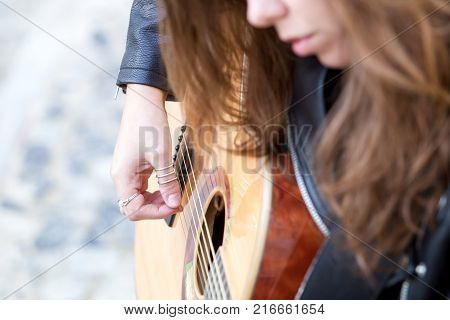 Closeup portrait of young woman with rings on fingers playing guitar. Music and creative concept.