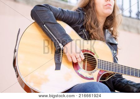 Closeup of acoustic guitar and woman hand on strings. Music and creative concept.