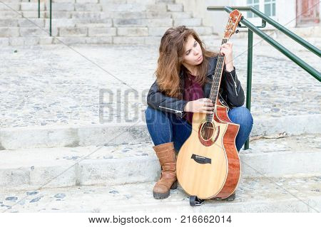 Portrait of young woman with guitar sitting on stairs and picking song. Creativity concept.