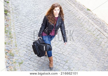 Focused young woman walking down street and carrying gyg bag with guitar. Female guitar player going to work in bar or club. Creative work concept.