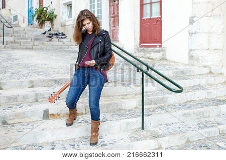 Portrait of young woman with guitar standing on stairs in street and texting message. Communication concept.