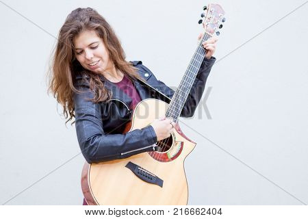 Portrait of smiling young woman playing guitar and looking away in grey background. Music and creative concept.