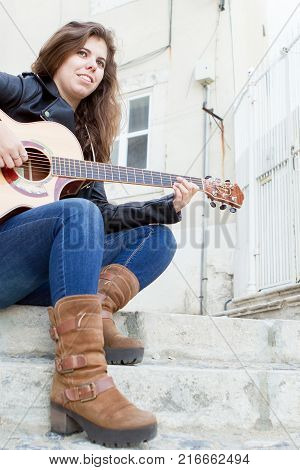 Portrait of smiling young woman sitting on stair in street and playing guitar. Creativity concept