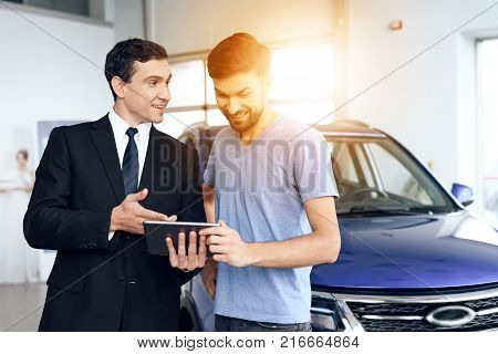 A man buys a new car in a light large car showroom. He is assisted by a dealer at the car dealership. There are many modern cars.
