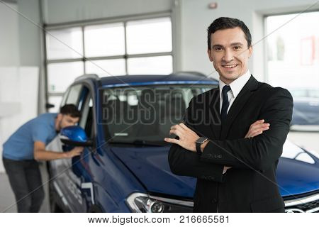 They are very happy about this, they are in a good mood. There are many modern cars.