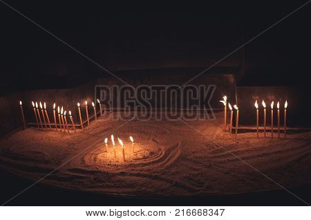 Flaming candles. Golden light of candle flame. Sacred burning candles in the church. Church candles background.