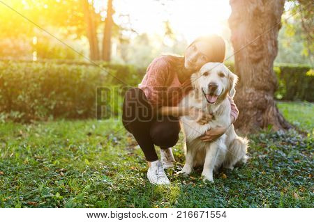 Image of woman hugging dog on lawn in summer park