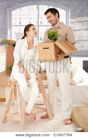 Young happy couple moving to new house, unpacking boxes, mess around, smiling.?