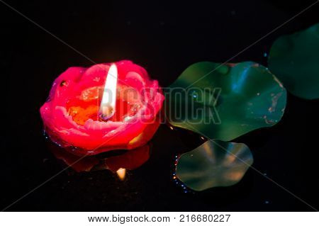 A floating red candle amonst some lily pads in a pond.