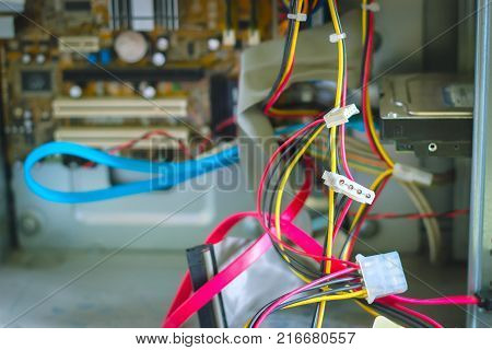 Old computer system unit wires with spiderweb and dust inside at purple background