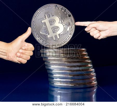 On a blue background are silver coins of a digital crypto currency Bitcoin. In addition to the lying coins there is standing bitcoin. On one side pushes finger in the bitcoin and on the other side supports his thumb. Stabilized value.