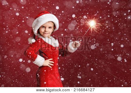 Christmas, x-mas, winter, happiness concept - smiling little girl in Santa Claus dress with sparkler. Snow falling.