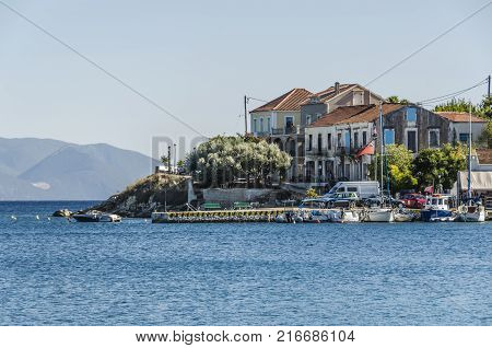 close-up of the dock of the fiskardo village with boats and their ancient constructions and in the background the mountains of the island of kefalonia greece