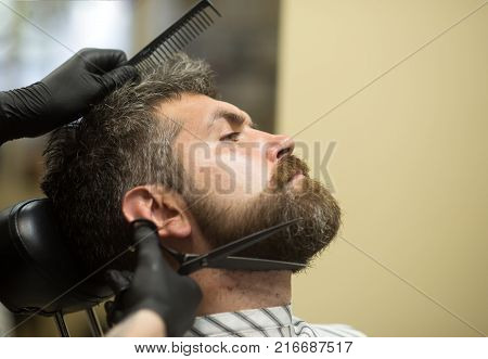 Haircut of bearded man archaism. Barber and hairdresser future. Fashion and beauty innovation. Man cut long beard and mustache with scissors. Hipster with serious face in barbershop new technology.