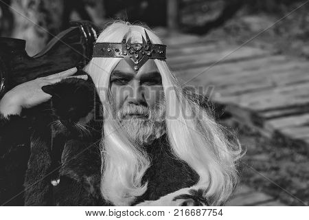 Druid old man with long silver hair beard with crown with black cat on shoulder in fur coat on blurred background