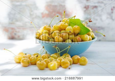 Yellow cherry in a bowl on the background of a vintage brick wall
