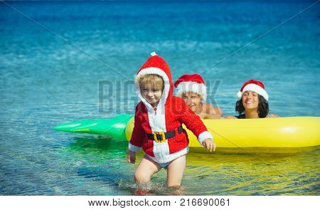 Winter holiday vacation. Christmas happy family on pineapple mattress in water. Xmas party celebration fathers and mothers day. Santa child parents at Christmas. New year man girl with small boy.