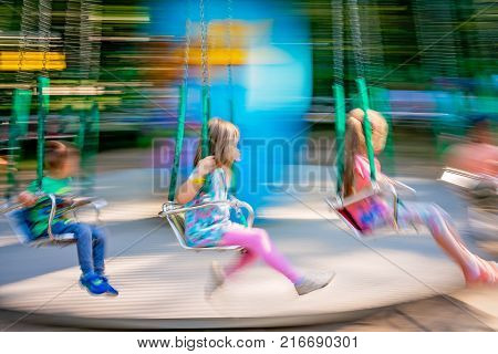 Unidentifiable children riding on a carousel in an amusement park, image with intentional movement blur