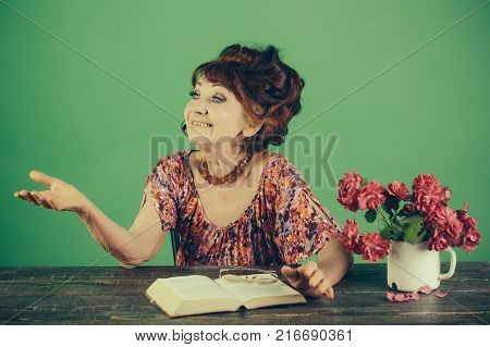 Teacher or professor education teachers day. Pension and retirement old age. Writer and poet granny read fairytale. happy old lady or grandmother. Old woman reading book with glasses at flowers.