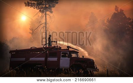 firefighter on a fire truck extinguishes wildfire