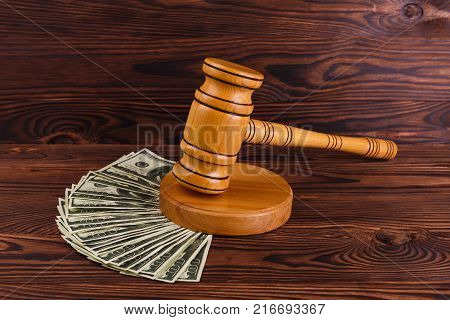 A lot of dollar bills and a wooden auction hammer on a wooden background. Details of the auction.