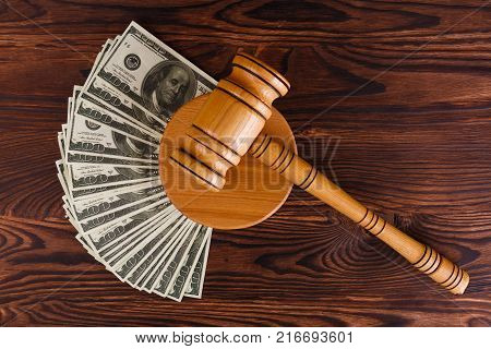 A wooden auction hammer on a wooden stand, next to a lot of dollar bills. Details of the auction. View from above.
