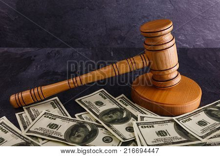 On a dark background, there is a wooden stand with a hammer auctioneer, and next to a lot of dollar bills. Details of the auction.