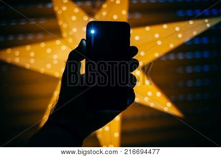 Man Holding The New Phone With Yellow Star Bokeh Background Featuring A Blick Light From The Rear Fl