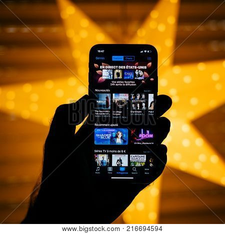 PARIS FRANCE - NOV 10 2017: Man holding the new Apple iPhone X 10 Display with yellow star bokeh background featuring series and movies in the itunes app