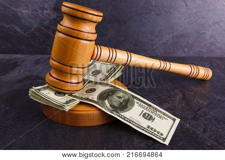 A few dollar bills are between the wooden stand and the wooden hammer of the auctioneer. Details of the auction. Auction business.